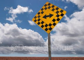 Both ways yellow sign on blue sky.