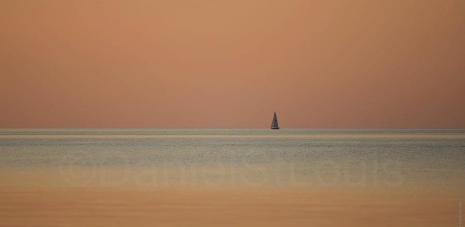 Sail boat on a peach sky.