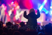 Little girl on dad's shoulders at concert in the park in Moncton.